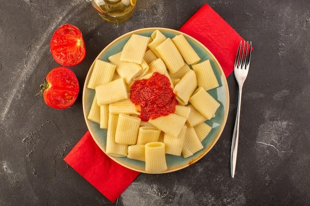 Вид сверху приготовленная итальянская паста с томатным соусом внутри тарелки
