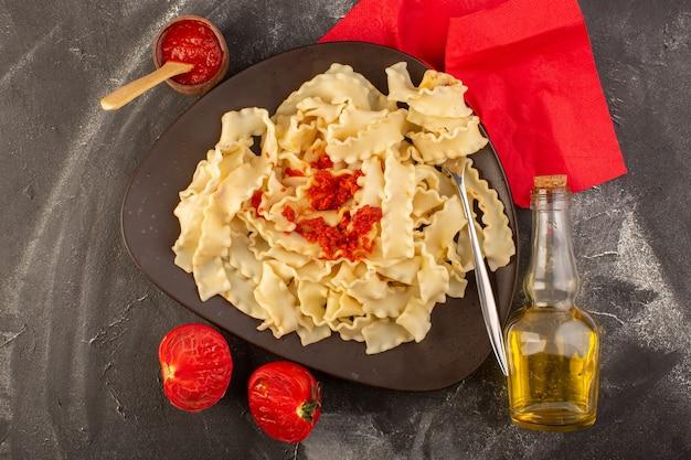 平面図は、灰色のテーブルフード食事イタリアンパスタのプレート内トマトソースのイタリアンパスタを調理
