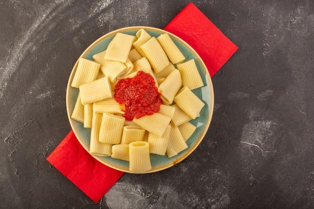 Вид сверху приготовленные итальянские макароны с томатным соусом внутри тарелки