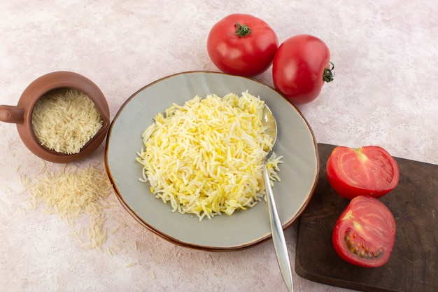 Вид сверху приготовленный рис внутри тарелки со свежими красными помидорами на розовом столе, еда, еда, овощной вкус