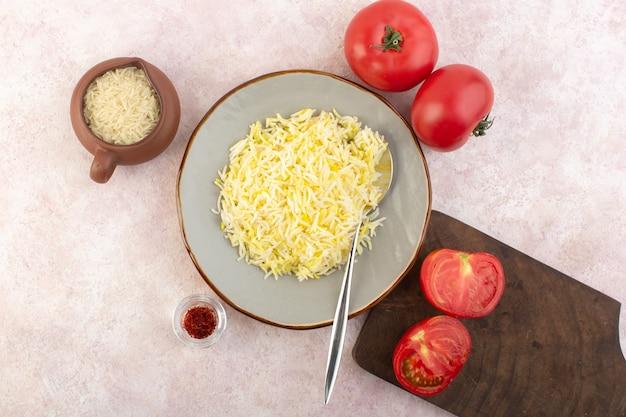 Вид сверху приготовленный рис со свежими красными помидорами на розовом столе еда еда овощной цвет