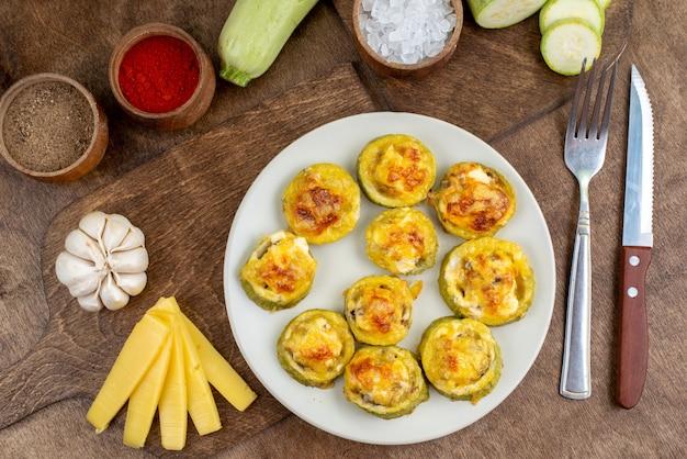 Вид сверху, приготовленные круглые тыквы внутри белой тарелки со свежими кабачками, соленым сыром и чесноком на деревянном фоне, еда, ужин, блюдо, овощ