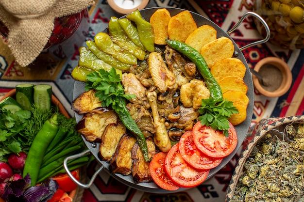 トップビュープレート上の赤いトマトグリーンピーマンブラックナスとジャガイモなどの野菜を調理