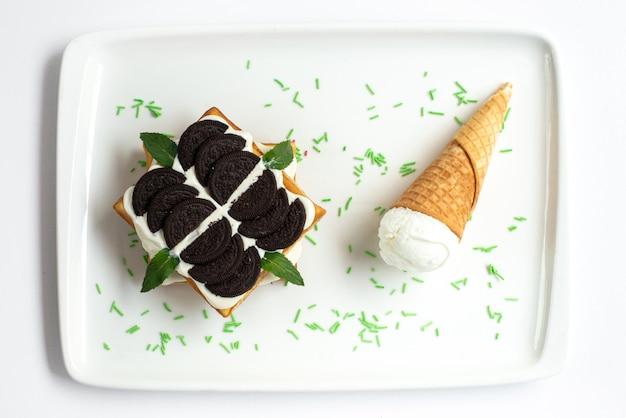 Торт с печеньем, вид сверху, торт на основе шоколадного печенья с заварным кремом и мороженым внутри белого стола, сладкое сахарное печенье.