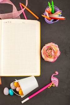 トップビューのお手本と暗い机色のキャンディー写真の花にカラフルなキャンディーとキャンドルと花