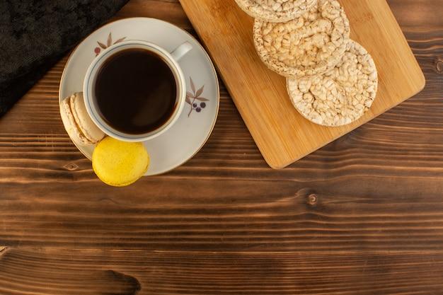 茶色の木製の素朴なテーブルコーヒーホットドリンクにフランスのマカロンとクラッカーとホットで強いコーヒーのトップビューカップ