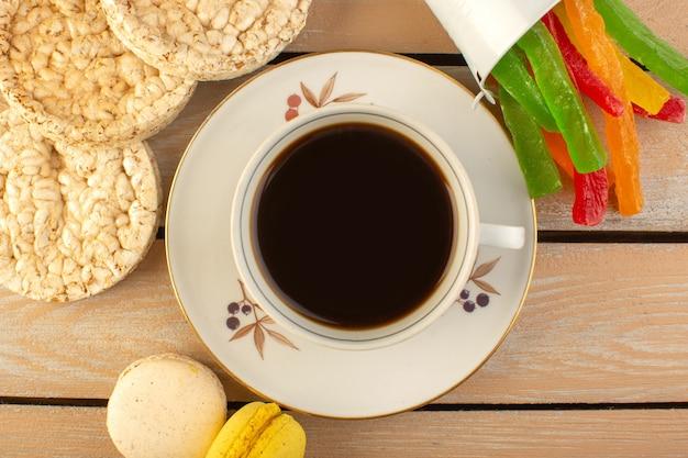 クリーム色の素朴なデスクでフレンチマカロンとマーマレードを使ったホットで強いコーヒーのトップビューカップコーヒーコーヒーの写真強いお菓子