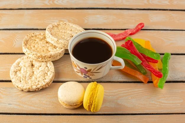 クリーム色の素朴なデスクでコーヒーマッシュとフレンチマカロンとマーマレードを使ったホットで強いコーヒーのトップビューカップコーヒーの写真強い