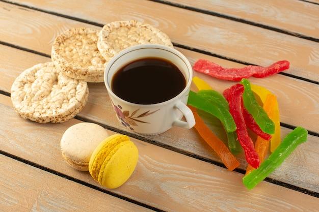 クリーム色の素朴なデスクにフレンチマカロンとマーマレードがあり、コーヒーフォトシュガーを飲むホットで強いコーヒーのトップビューカップ
