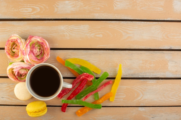 Чашка горячего и крепкого кофе, вид сверху, с французскими макаронами и мармеладом на кремовом деревенском столе пить кофе фото сладкое печенье сахар