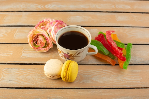 Чашка горячего и крепкого кофе, вид сверху с французскими макаронами и мармеладом на кремовом деревенском столе пить кофе фото сладкое печенье