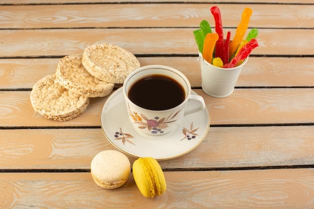 Чашка горячего и крепкого кофе, вид сверху с французскими макаронами и мармеладом на кремовом деревенском столе напиток кофе фото крепкий