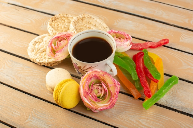 トップビューカップのコーヒーホットと強いフランスのマカロンの花とクリーム色の素朴なデスクにマーマレードと強いコーヒーを飲む強い写真
