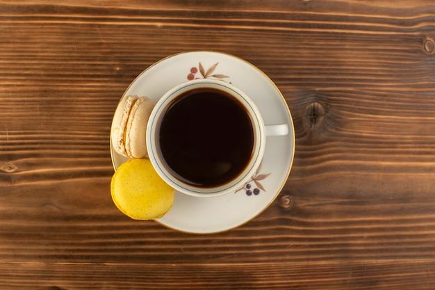 茶色の木製の素朴なデスクコーヒーホットドリンクにフランスのマカロンとホットで強いコーヒーのトップビューカップ