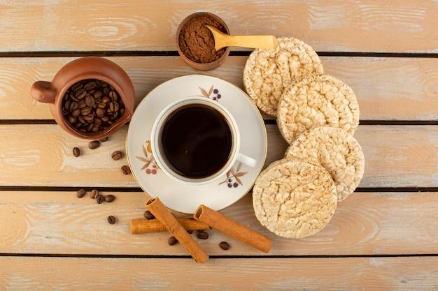 新鮮で茶色のコーヒーの種子とクリームの素朴なデスクのコーヒー種子ドリンク写真穀物のクラッカーとホットで強いコーヒーのトップビューカップ
