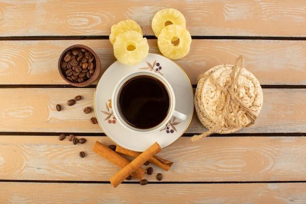 新鮮で茶色のコーヒーシードシナモンとクリームの素朴なデスクのコーヒーシードドリンク写真穀物のクラッカーとホットで強いコーヒーのトップビューカップ