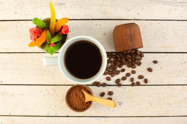 新鮮な茶色のコーヒーの種子と白いカップでコーヒーのトップビューカップ