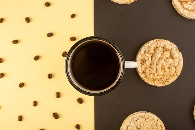 茶色のコーヒーの種子とクラッカーとコーヒーのトップビューカップ