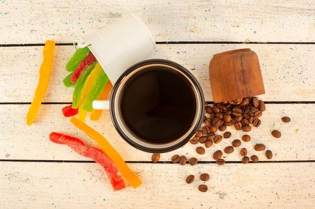 新鮮な茶色のコーヒーの種子とカラフルなマーマレードとコーヒーのトップビューカップ