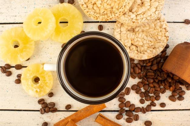 Чашка кофе сверху со свежими коричневыми кофейными семечками и крекерами с корицей