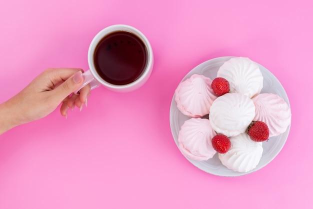 Чашка чая, вид сверху вместе с безе и клубникой внутри тарелки на розовом, цвете чайного бисквитного торта