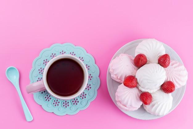 Чашка чая, вид сверху, красная клубника и безе на розовом бисквитном кондитерском изделии