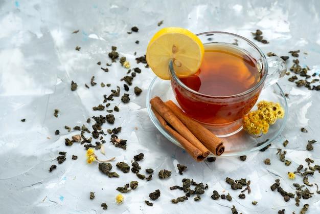 Чашка чая с лимоном и корицей на ярких жидких фруктах, вид сверху
