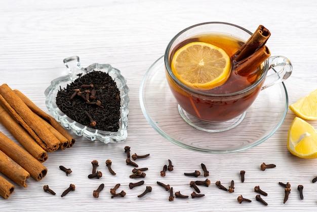 Чашка чая с лимоном и корицей на белом, чайный десерт, вид сверху