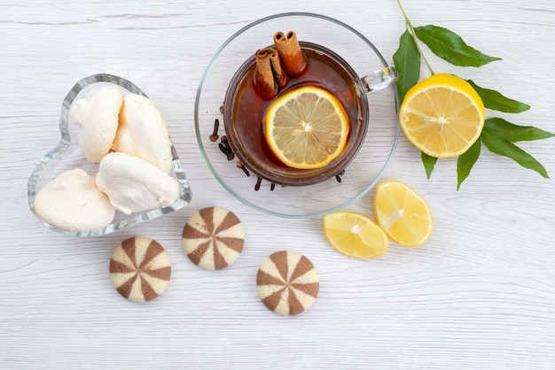 Чашка чая с лимонным печеньем и корицей на белом, чайный десерт, вид сверху