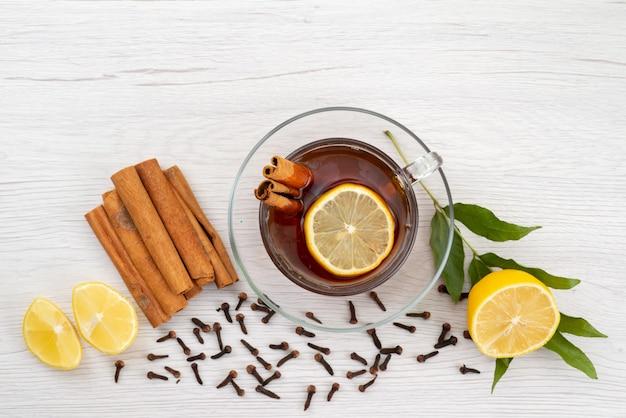 Чашка чая с лимонной мятой и корицей на белом, вид сверху, десертные конфеты