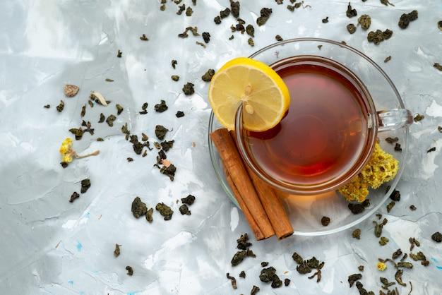 Чашка чая, вид сверху с долькой лимона и корицей на ярких жидких фруктах