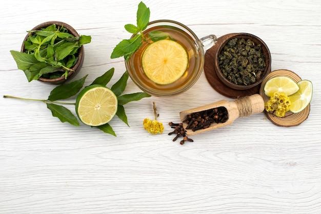 Чашка чая с мятой и лимоном на белом, вид сверху, жидкий фруктовый чай