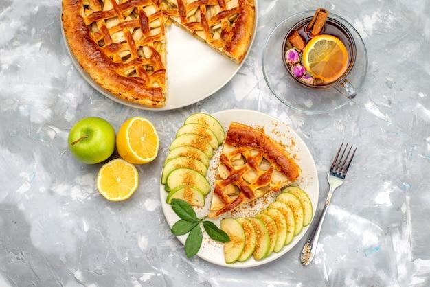 Вид сверху вкусный яблочный торт внутри тарелки с чаем и свежим зеленым яблоком на сером письменном столе, печенье, сахар