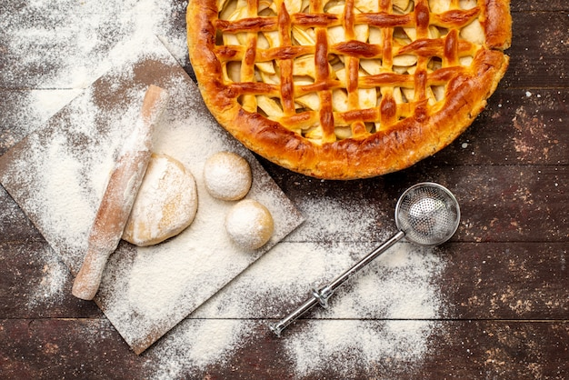 Вид сверху вкусный яблочный торт круглой формы из муки и теста на темном фоне торт бисквитный сахар фрукты