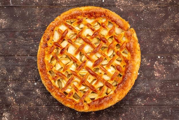 茶色の背景のケーキビスケットシュガーフルーツの上に丸型のおいしいアップルケーキのトップビュー