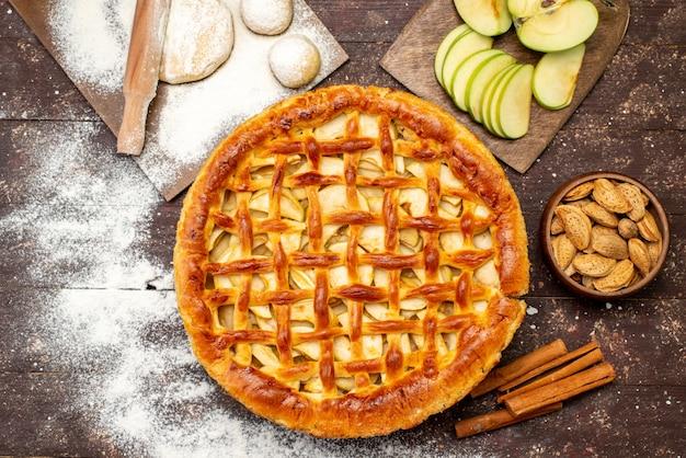 Вид сверху вкусный яблочный пирог круглой формы с корицей свежие яблоки и тесто на темном фоне торт бисквитный сахар фрукты