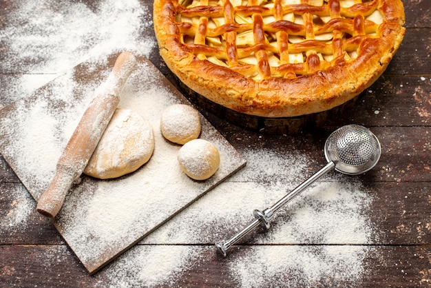 Вид сверху вкусный яблочный торт круглой формы с мукой и тестом на темном фоне торт бисквитный сахар фрукты