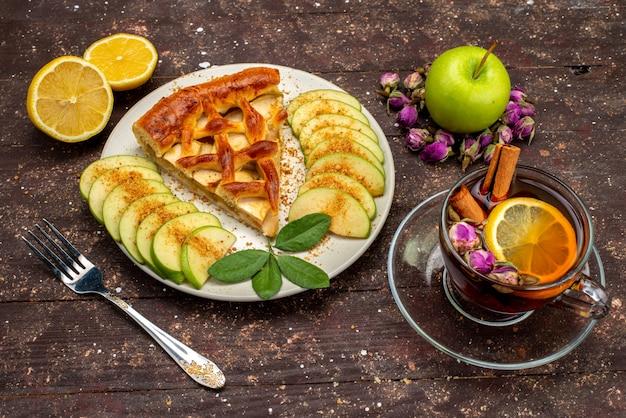 Вид сверху вкусного яблочного торта внутри тарелки с чаем свежее зеленое яблоко на деревянном столе торт бисквитный сахар