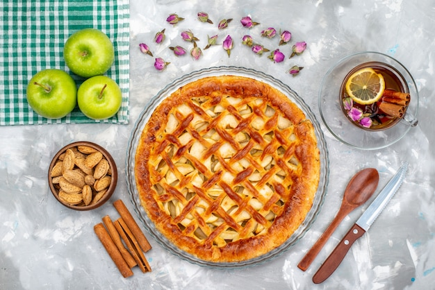 Вид сверху вкусный яблочный пирог со свежими зелеными яблоками, чай и коричный пирог, печенье, сахар, фрукты