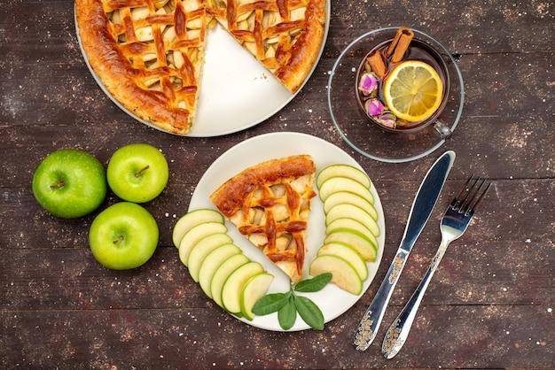 Вид сверху вкусный яблочный пирог с чаем свежие зеленые яблоки на деревянном столе торт бисквитный сахар