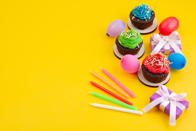 Вид сверху вкусных шоколадных пирожных на основе конфет и шариков на желтом, конфетном бисквитном цвете