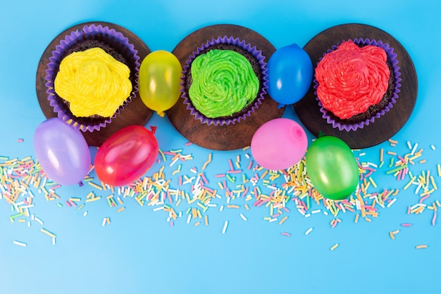 Вид сверху восхитительных пирожных внутри пурпурного цвета формирует шоколадную основу вместе с конфетами на синем, конфетном бисквитном цвете.
