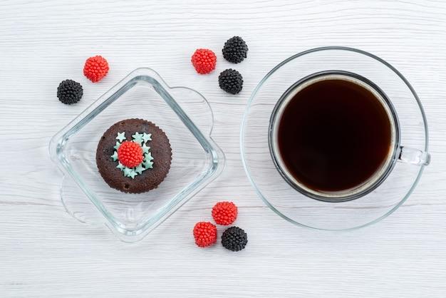 Вид сверху вкусного коричневого внутри фиолетовой формы с чашкой чая на белом, конфеты цвета конфеты