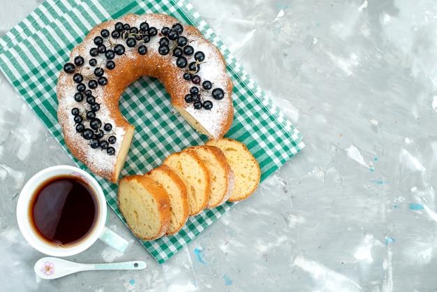 Вид сверху вкусный торт со свежей черникой и чаем на белом столе, торт чайная ягода