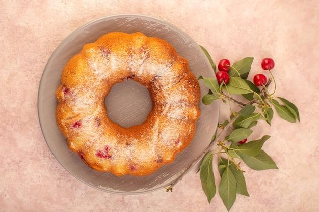 Вид сверху вкусный вишневый торт круглый, сформированный внутри серой тарелки на розовом письменном столе, печенье, сахар, сладкое