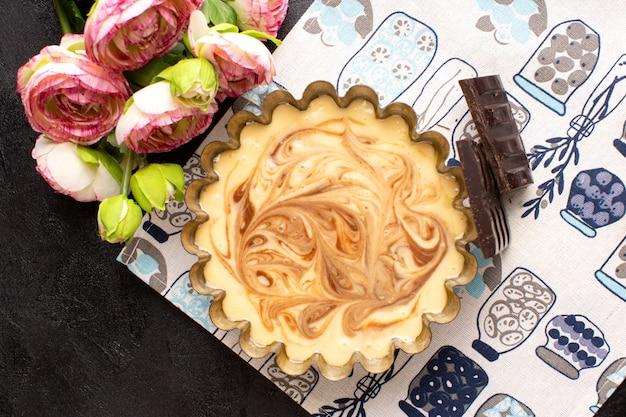 Вид сверху вкусный кофейный торт сладкий шоколадный вкусный кондитерский торт сладкий вместе с розами на темном столе