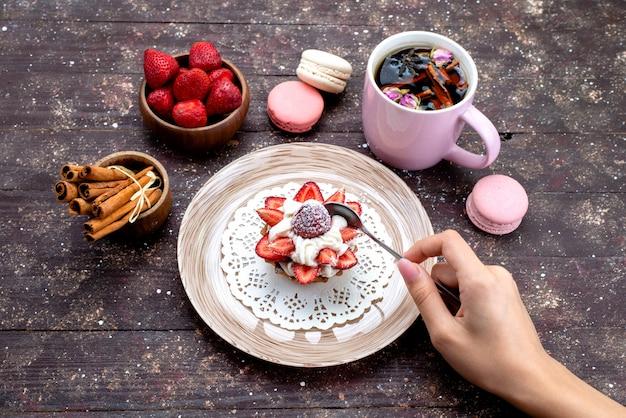Вид сверху вкусный маленький торт со сливками и свежими нарезанными фруктами вместе с корицей и макаронами на коричневом бисквите фруктовый торт на столе