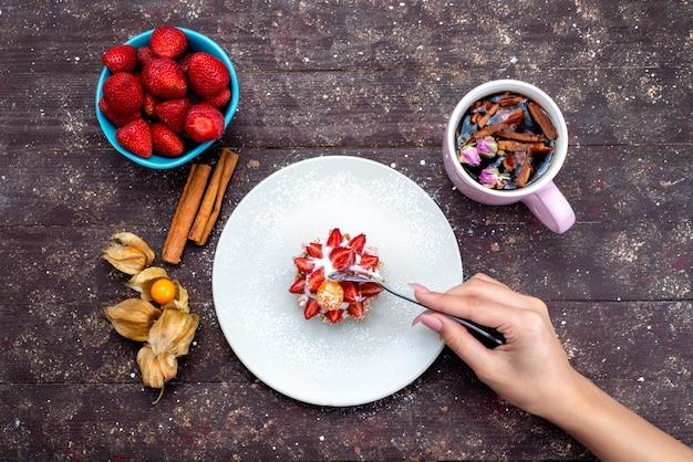Вид сверху вкусный маленький торт со сливками и свежими нарезанными фруктами вместе с корицей и клубникой на коричневом бисквите фруктового торта на столе