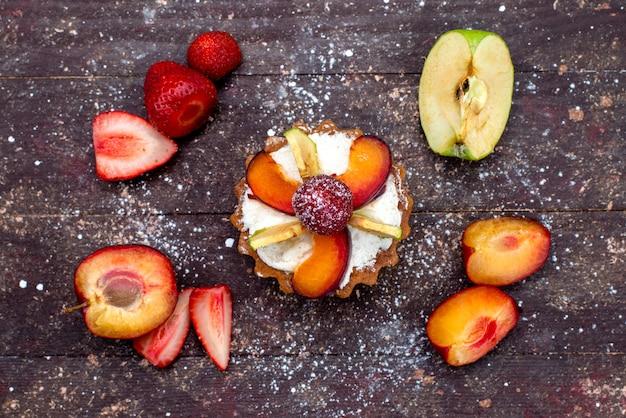 Вид сверху вкусный маленький торт со сливками и свежими нарезанными фруктами на коричневом столе фруктовый торт бисквит сахарный чай