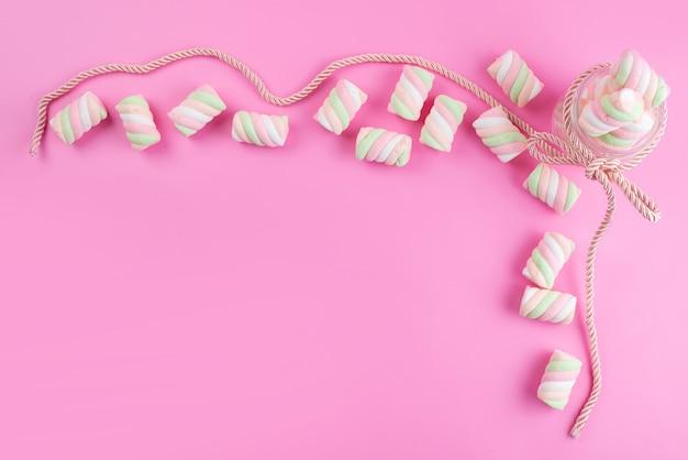Вид сверху вкусного зефира на розовых, цветных сахарных конфетах